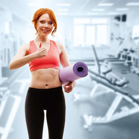 red -haired woman holding fitness mat in the gym photo