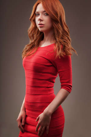 girl in red dress: sexual woman wearing red dress over dark background