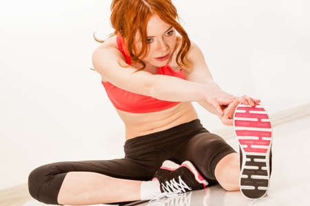 hamstring: red woman stretching her foot on the floor