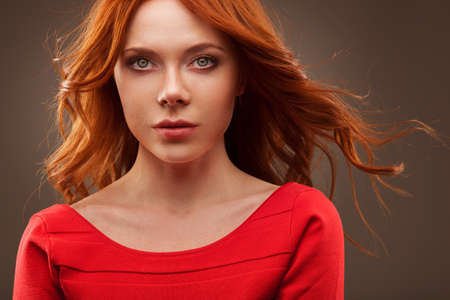 red hair woman: closep portrait of sexual woman wearing red dress over dark background