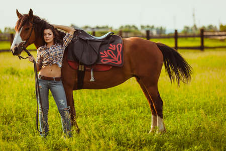 brunette cowgirl woman standing with horse on field Stock Photo - 21928717