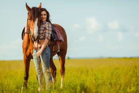 cowboy on horse: brunette cowgirl woman posing with horse outdoors portrait Stock Photo