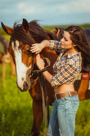 brunette cowgirl woman standing with horse outdoors portrait photo