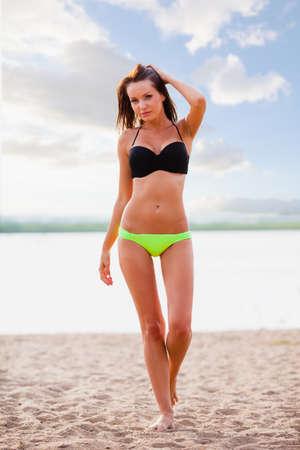 beautiful sexy brunette woman wearing bikini walking on beach