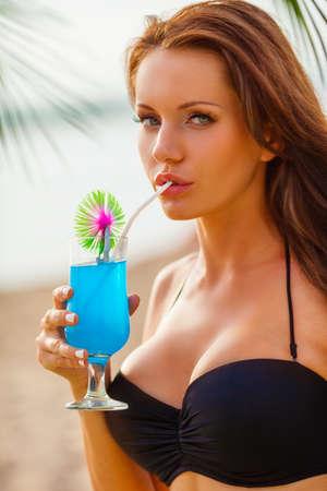 schöne sexy Brünette Frau trägt Bikini trinken blauen Cocktail