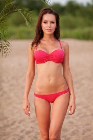 woman panties: beautiful sexy brunette woman wearing pink bikini walking on beach