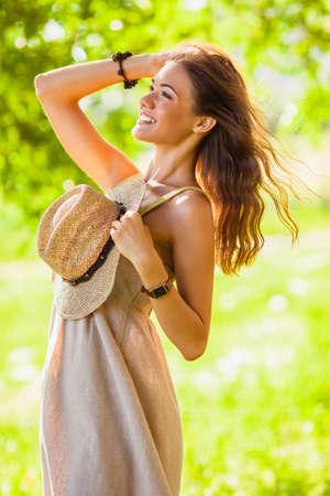 happy girl wearing straw walking in the green summer park