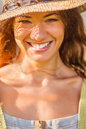 laughing girl wearing straw walking in the green summer park, closeup face portrait photo