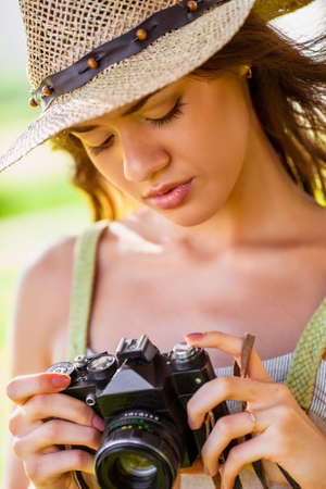 happy young girl looking to vintage camera walking outdoors in the park photo