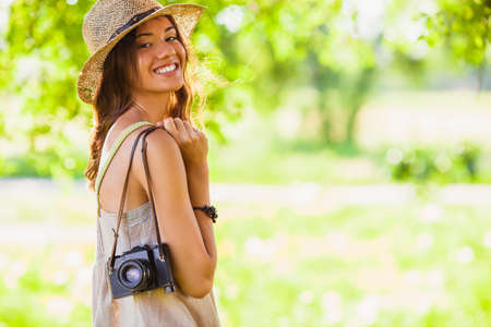 straw hat: happy young girl wearing straw hat with vintage camera walking in the park, copy space from the right side Stock Photo