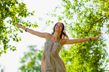 rising of sun: feliz niña llevaba hedphones aire libre y el aumento de su cabeza