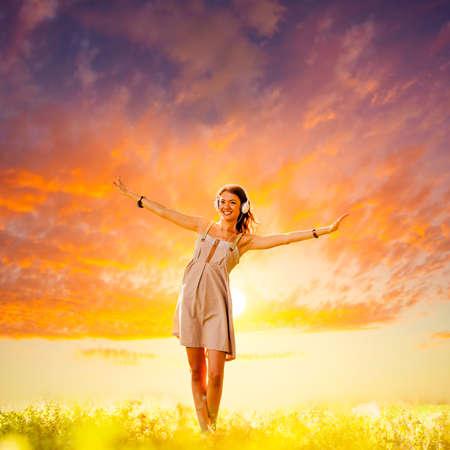 la escucha activa: hermosa chica con auriculares caminando en la puesta del sol Foto de archivo