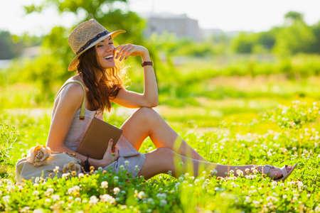 schöne Mädchen tragen Hut mit Buch auf Gras zu sitzen
