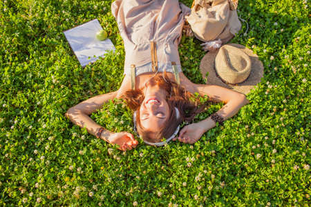 happy woman wearing headphones lying on grass with closed eyes photo