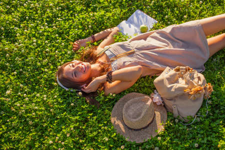 happy woman wearing headphones lying on grass photo