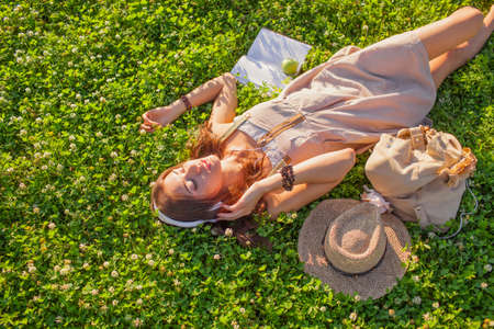 happy woman with closed eyes wearing headphones lying on grass photo