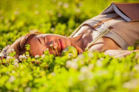 happy beautiful relaxing woman lying on grass with apple
