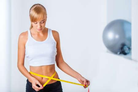 young beautiful woman measuring her waistline Stock Photo