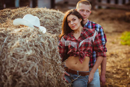 young adult couple embracing near hay photo