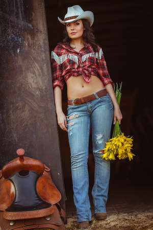 country lifestyle: young adult woman wearing country style wear posing near door with flowers and saddle Stock Photo