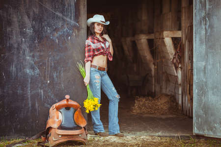 cowgirls: young adult woman wearing country style wear posing near door with flowers and saddle Stock Photo