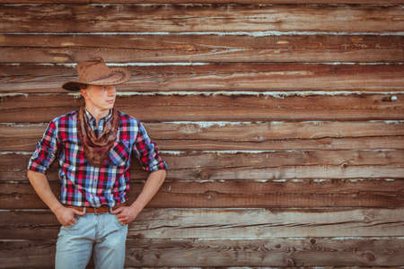 young adult cowboy style man on stable photo