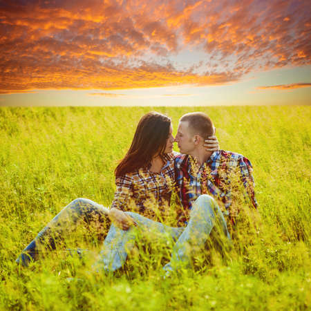 field glass: young adult couple sitting in the field over sunset Stock Photo