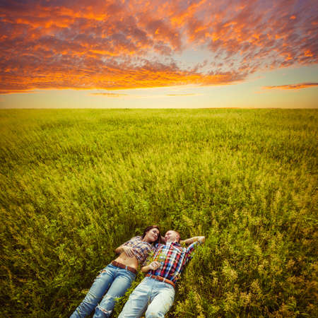 happy young adult couple lying on the grass over sunset photo