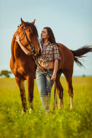 young beautiful woman standing near a horse photo