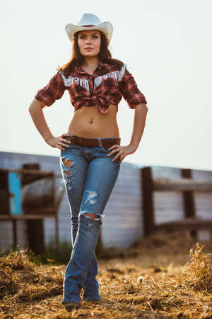 young adult woman wearing country style posing on farmland photo