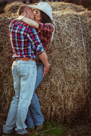 young adult couple kissing near hay Foto de archivo