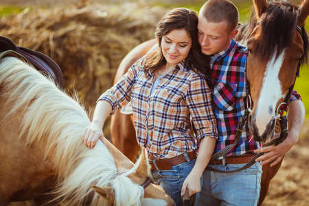 young adult couple standing on farm with horses, closeup photo photo