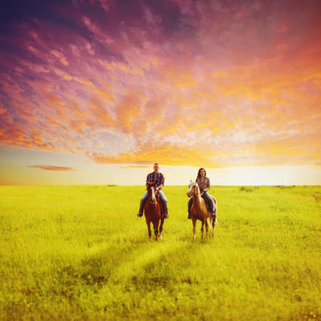 young adult copule riding on horses over sunset photo