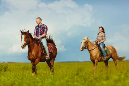 loving couple riding on horses across the field over cloudy skies Stock Photo