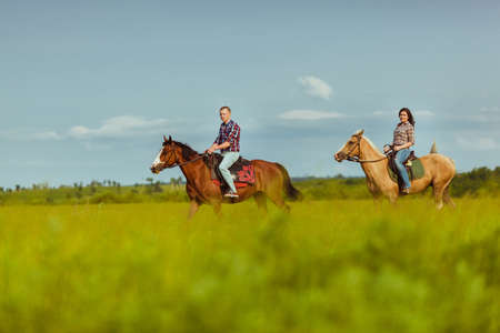 loving couple riding on horses across the field over blue skies Foto de archivo