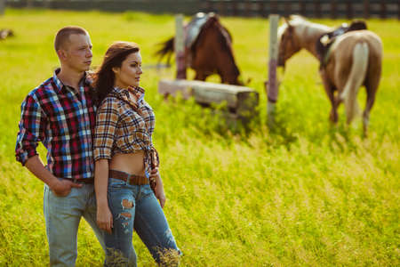 young adult cowboy style couple standing on farm with horses
