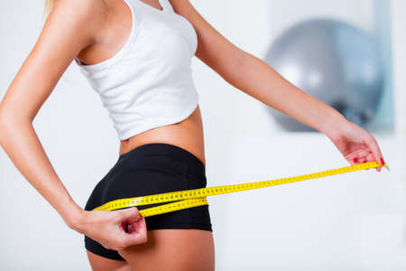 sports woman measuring her buttocks with yellow tape Stock Photo