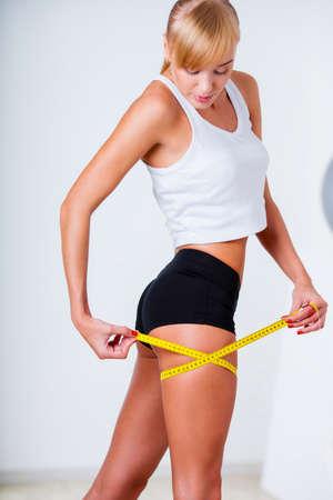 cintas metricas: mujer rubia que mide sus caderas y mirando a la cinta Foto de archivo