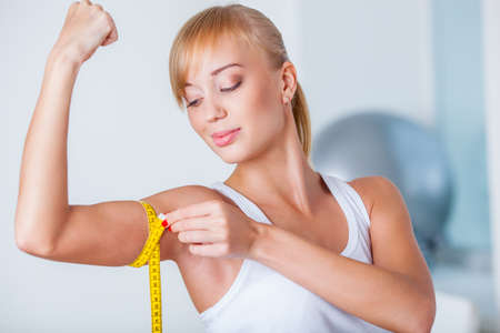 bicep: young beautiful blonde woman measuring her biceps with tape Stock Photo