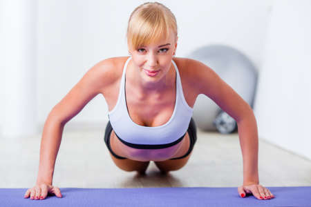 blonde woman doing push-ups on the mat photo