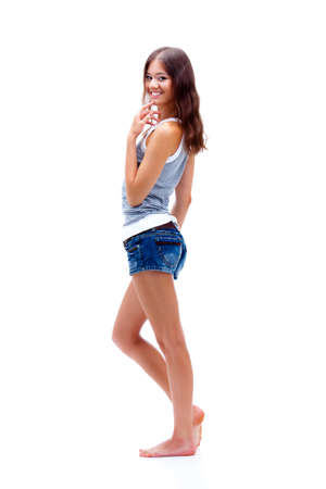 barefoot teens: girl standing on white background, wearing shorts