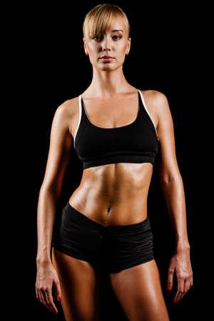 fitness motivation: sports woman portrait wearing black sportswear over dark