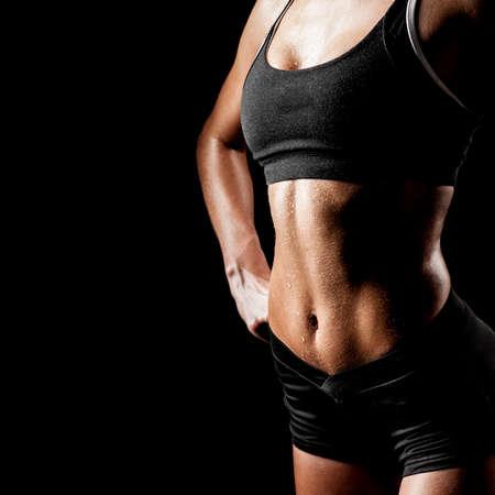 sports woman portrait wearing black sportswear over dark