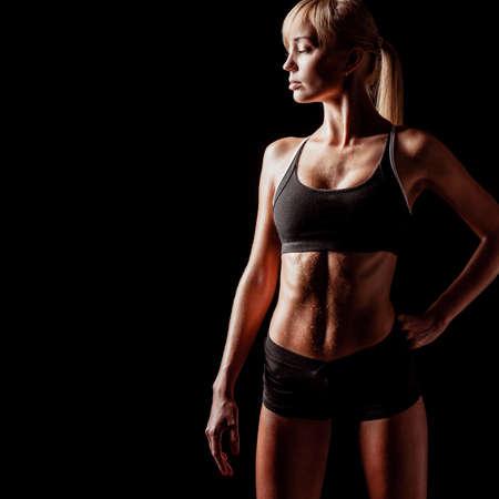 sports woman portrait wearing black sportswear over dark, looking to the side Stock Photo