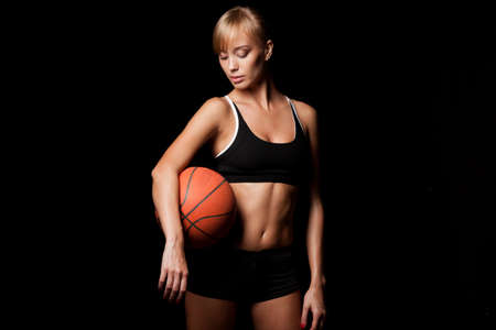 woman standing with basketball over black background photo