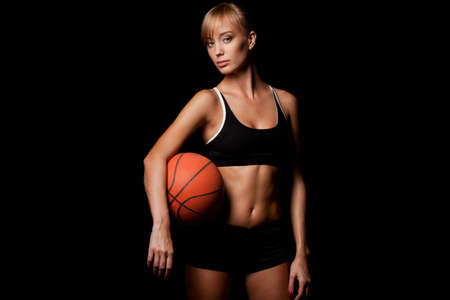 baloncesto chica: mujer de pie con el baloncesto sobre fondo negro