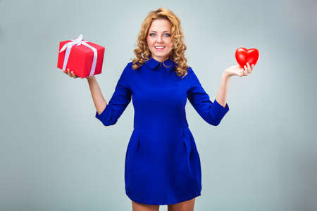 blue gift box: happy blonde woman wearing blue dress holding red heart and gift box