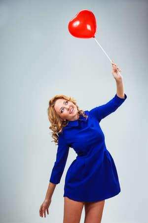 donna volante: donna bionda volare via con colore rosso a forma di cuore palloncino