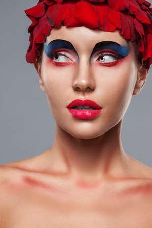 maquillaje de fantasia: closeup retrato de la cara de la mujer con maquillaje creativo y pétalos de rosa sobre la cabeza