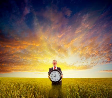 businesswoman standing on field before the sunset and holding big clock photo